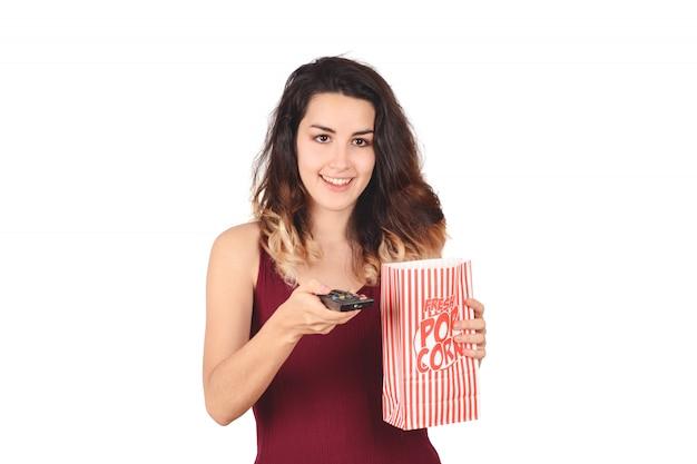 Jonge vrouw die op een film let en popcorn eet