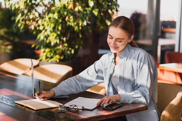 Jonge vrouw die op een klembord schrijft