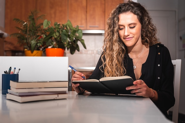 Jonge vrouw die op een notitieboekje schrijft