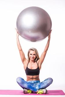 Jonge vrouw die op een pilatesbal leunt die over een witte muur wordt geïsoleerd
