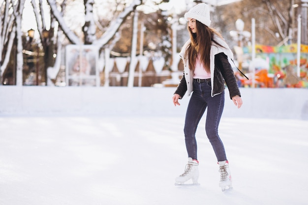 Jonge vrouw die op een piste in een stadscentrum schaatst