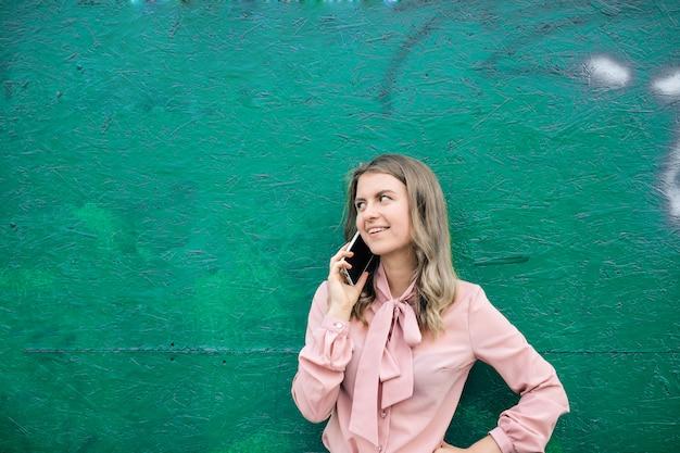 Jonge vrouw die op een smartphone spreekt