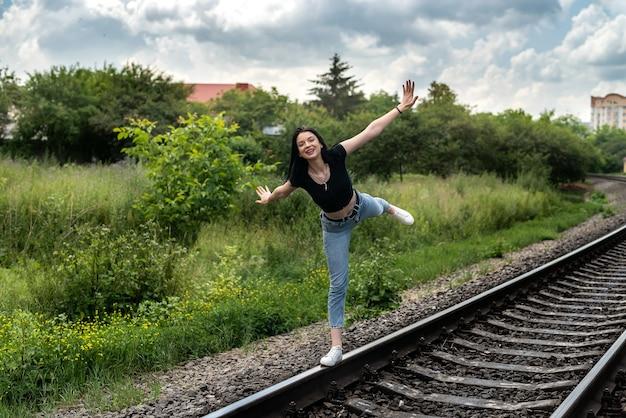 Jonge vrouw die op een spoorlijn staat