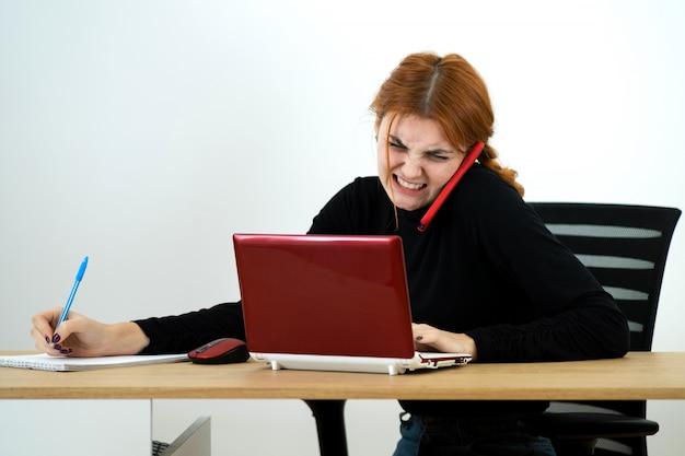 Jonge vrouw die op een telefoonzitting bij een bureau met laptop en notitieboekje spreekt.