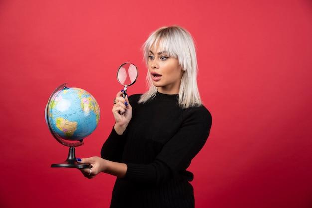 Jonge vrouw die op een wereldbol met loep op een rode achtergrond kijkt