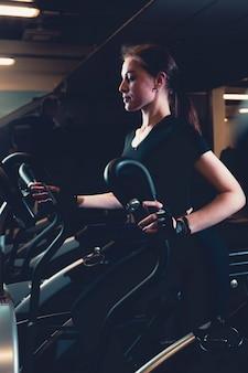 Jonge vrouw die op elliptische cardiomachine uitoefent