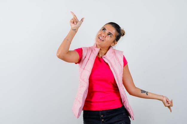 Jonge vrouw die op en neer wijst in roze t-shirt en jas en er geamuseerd uitziet