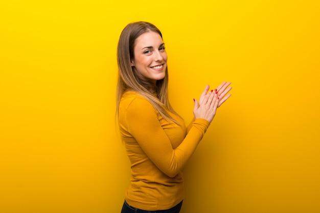 Jonge vrouw die op gele achtergrond na presentatie in een conferentie toejuicht