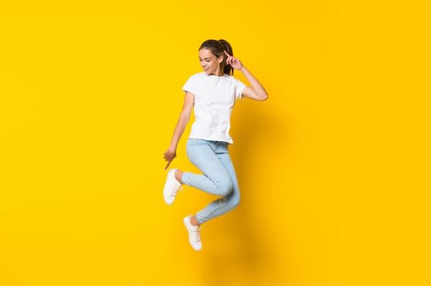 Jonge vrouw die op gele muur springt