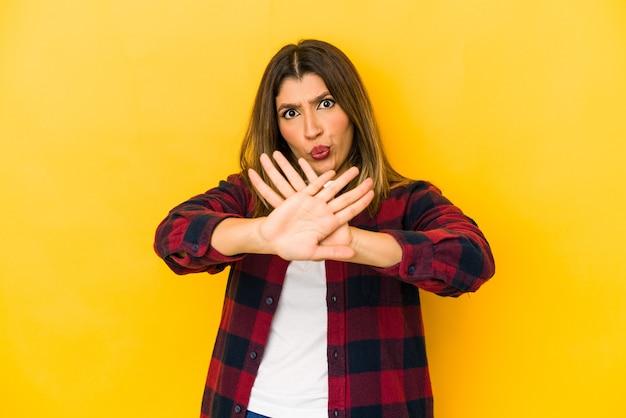 Jonge vrouw die op gele muur wordt geïsoleerd die een ontkenningsgebaar doet