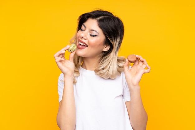 Jonge vrouw die op gele muur wordt geïsoleerd die kleurrijke franse macarons houdt en het eet
