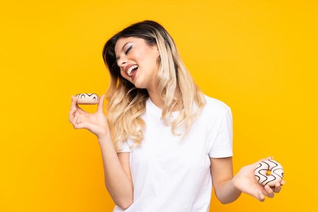 Jonge vrouw die op gele muurholding donuts wordt geïsoleerd met gelukkige uitdrukking
