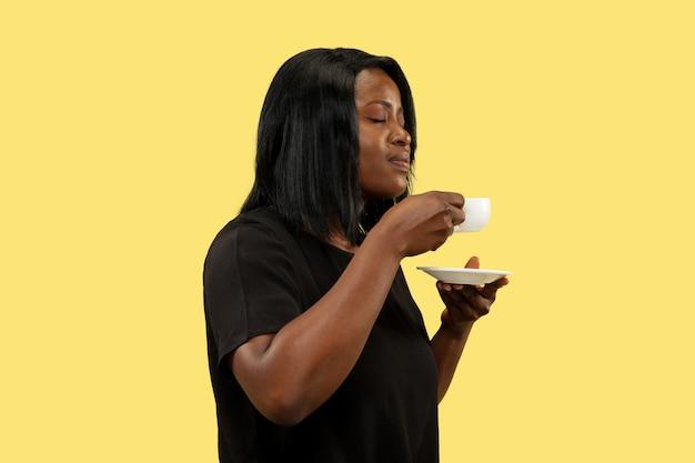 Jonge vrouw die op gele studiomuur wordt geïsoleerd