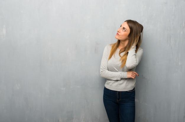 Jonge vrouw die op geweven muur een idee denkt terwijl het krassen van hoofd