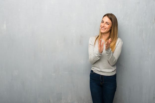 Jonge vrouw die op geweven muur na presentatie in een conferentie toejuicht