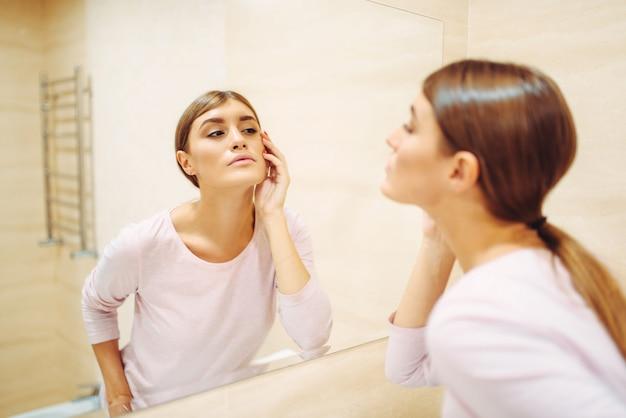 Jonge vrouw die op gezicht kijkt naar de spiegel in de badkamer.