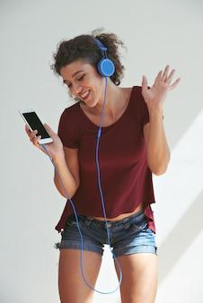 Jonge vrouw die op haar favoriete liedjes met hoofdtelefoons danst