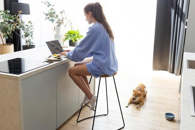 Jonge vrouw die op haar laptop werkt naast haar hond