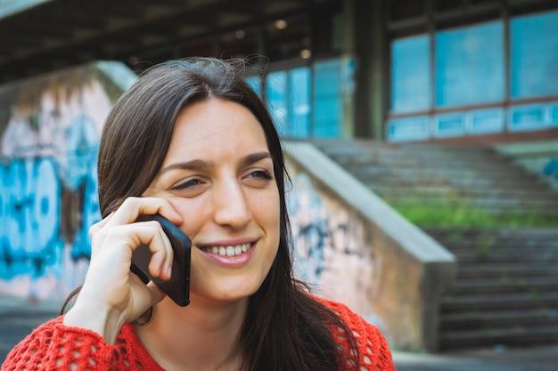 Jonge vrouw die op haar mobiele telefoon spreekt.