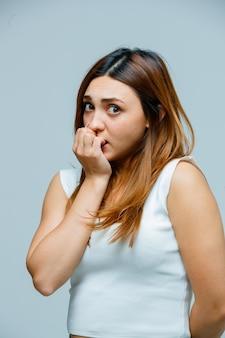 Jonge vrouw die op haar nagels bijt