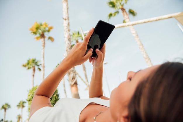 Jonge vrouw die op haar telefoon doorbladert