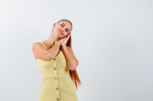 Jonge vrouw die op handpalmen als hoofdkussen in gele kleding leunt en ontspannen kijkt. vooraanzicht.