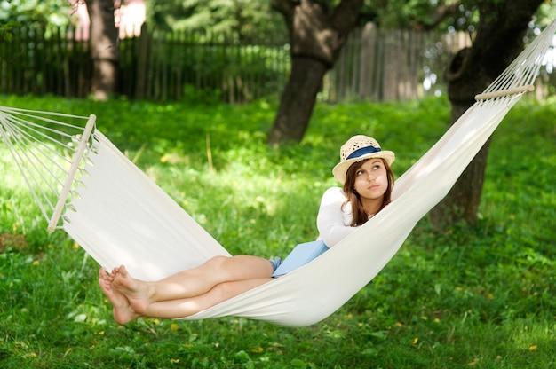Jonge vrouw die op hangmat ligt