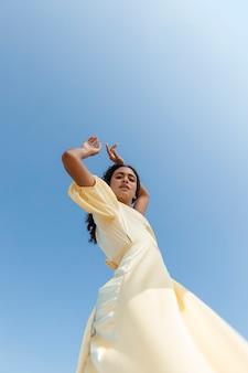 Jonge vrouw die op hemelachtergrond danst