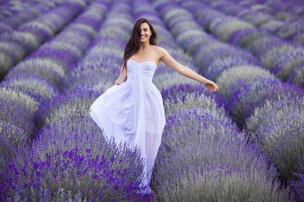 Jonge vrouw die op het lavendelgebied loopt. mooie vrouw op zomer bloemen achtergrond