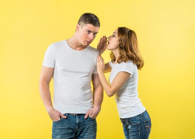 Jonge vrouw die op het oor van de vriend tegen gele achtergrond fluisteren