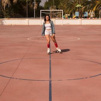 Jonge vrouw die op het openluchtvoetbalhof schaatst