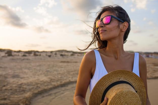 Jonge vrouw die op het strand glimlacht