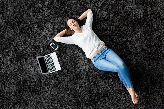 Jonge vrouw die op het tapijt legt