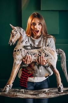 Jonge vrouw die op kerstmis houten poneystoel houdt