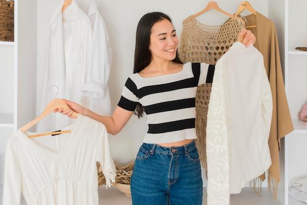 Jonge vrouw die op kleren probeert