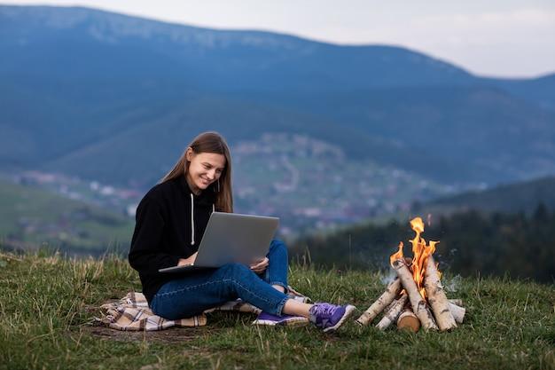 Jonge vrouw die op laptop in de bergen werkt