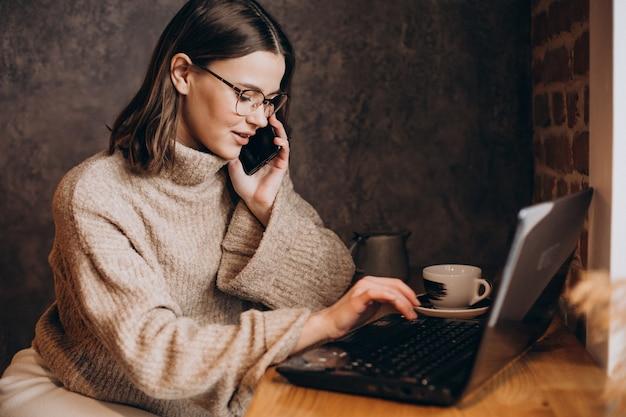 Jonge vrouw die op laptop in een café werkt