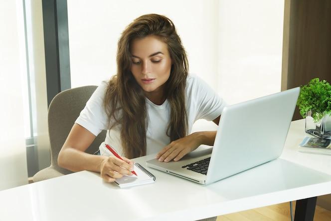 Jonge vrouw die op laptop pc werkt