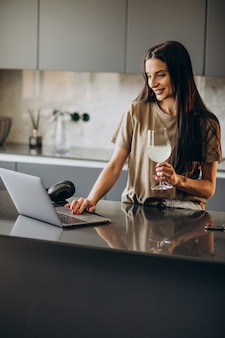 Jonge vrouw die op laptop van huis werkt