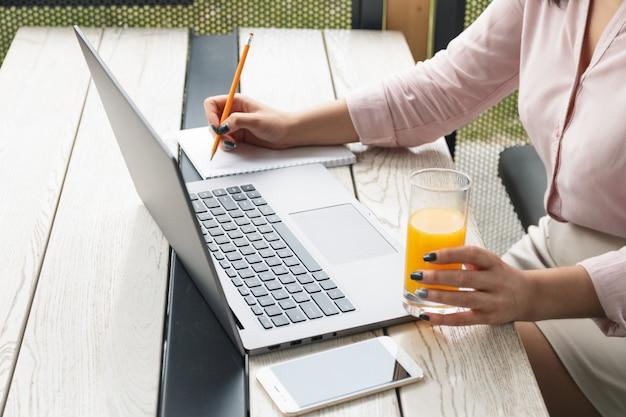 Jonge vrouw die op laptop werkt en schrijft, met een glas sinaasappelsap.