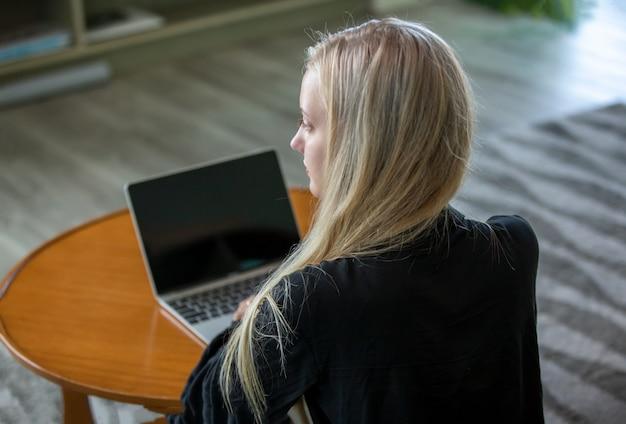 Jonge vrouw die op laptop werkt terwijl u thuis blijft.