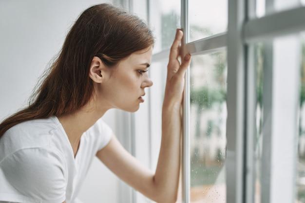 Jonge vrouw die op leunstoel thuis door het venster rust