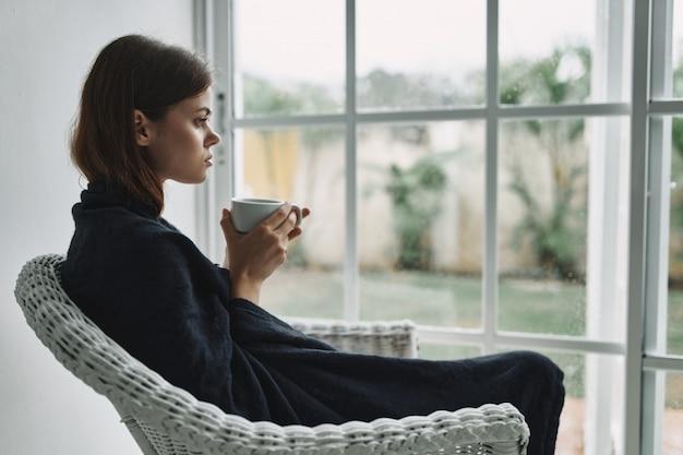 Jonge vrouw die op leunstoel thuis door het venster rusten