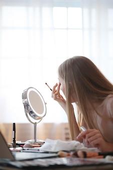 Jonge vrouw die op make-up zet.