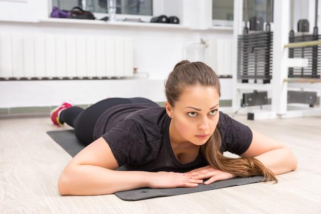 Jonge vrouw die op mat bij gymnastiek ligt
