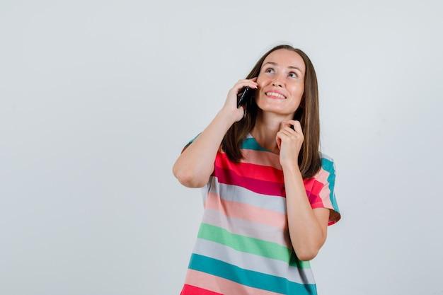 Jonge vrouw die op mobiele telefoon in t-shirt spreekt en gelukkig, vooraanzicht kijkt.