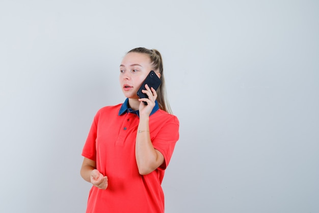 Jonge vrouw die op mobiele telefoon in t-shirt spreekt en peinzend kijkt