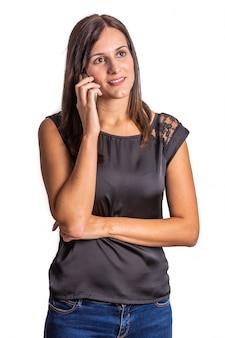 Jonge vrouw die op mobiele telefoon op witte achtergrond spreekt