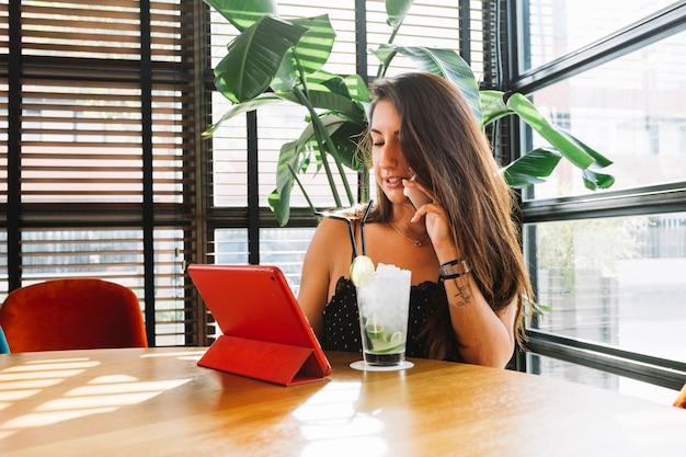 Jonge vrouw die op mobiele telefoon spreekt die digitale tablet met cocktailglas op lijst gebruikt