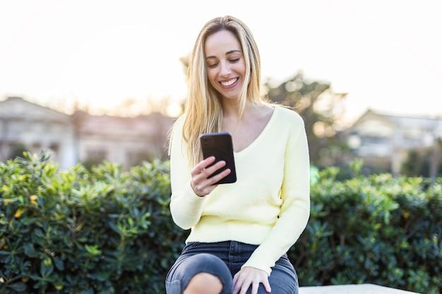 Jonge vrouw die op mobiele telefoon spreekt